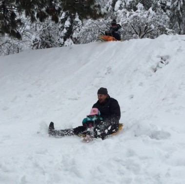 Emma going down the slope with her daddy.